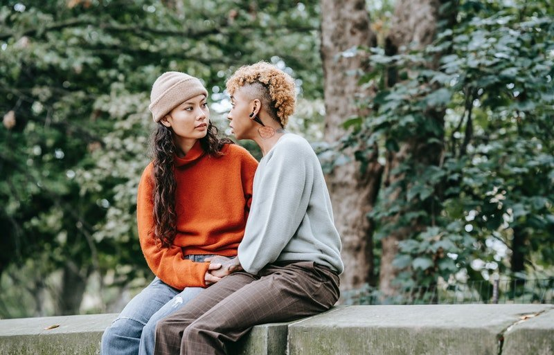 A same-sex couple, in discussion, sitting on a wall, surronded by trees.