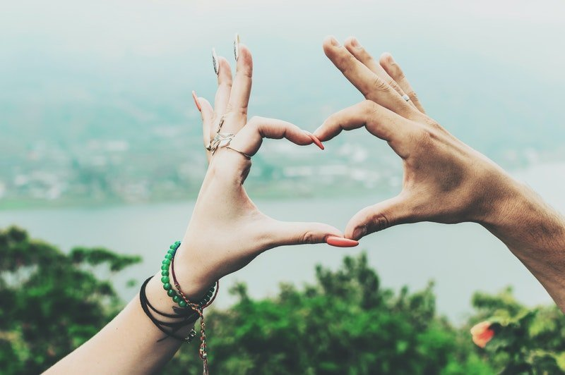 A male and female hand meeting together to make a heart sign